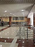 """Станция метро """"Митино"""" Балкон северного вестибюля. Балкон вестибюля оформлен в мягких тонах. Пол вымощен крапчатым полированным гранитом темно-бежевого оттенка - кофе с молоком. Массивные колонны поддерживают потолочную конструкцию оснащенной шумопоглощающей решеткой."""