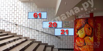 """Станция """"Новогиреево"""". Южный подземный вестибюль станции. Подуличный переход, выход пассажиров в город из стеклометаллических дверей налево. �нформационные указатели размером 1,2 х 0,4 м. Рекламные места №№ 61, 20, 21"""