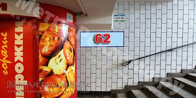 """Станция """"Новогиреево"""". Южный подземный вестибюль станции. Подуличный переход, выход пассажиров в город из стеклометаллических дверей налево. �нформационный указатель размером 1,2 х 0,4 м. Рекламное место №№ 62"""